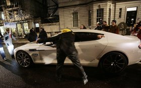 Protestors surround an Aston Martin in Lower Grosvenor Place, near Victoria in London